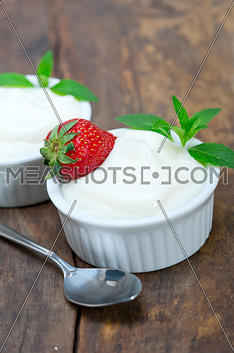 organic Greek yogurt and strawberry on a rustic wood table