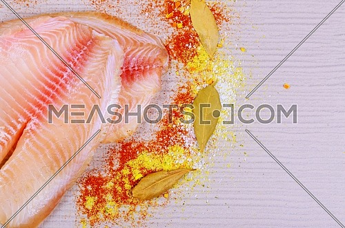 Above view raw fresh tilapia fillets over on cutting board