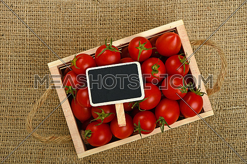 Fresh red ripe cherry tomatoes in small wooden box with black chalkboard price sign tag over jute burlap canvas background, top view