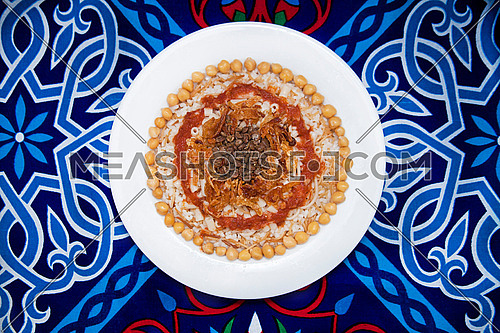 this is a shot for a Koshary plate on an oriental blue table cloth ... Considered one of the most famous dishes of Egypt, this vegetarian meal mainly contains rice, spaghetti, chick peas.
