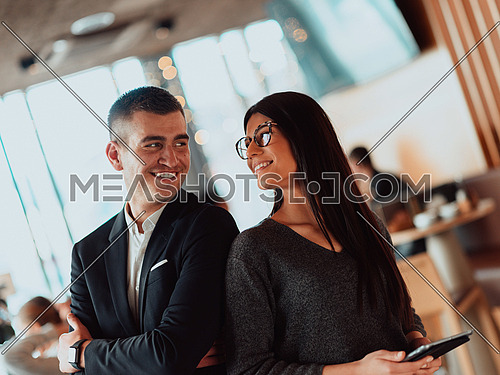 a portrait of two young people standing in an office and using a tablet