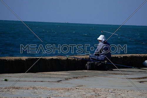 A man fishing in the Mediterranean sea in alexandria