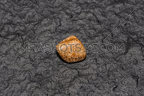 Jasper gemstone. isolated on black stone background. Macro shot.