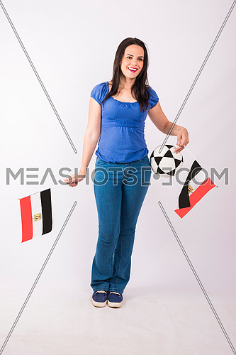 Young lady standing and holding two small egyptian flags, and ball on white background.