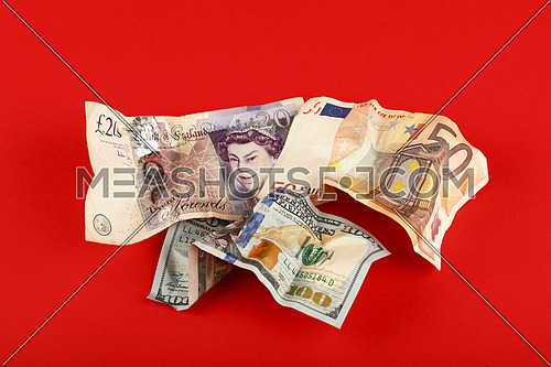 Close up crumpled paper currency banknotes of US dollar, Euro and British pound over red background with copy space, high angle view