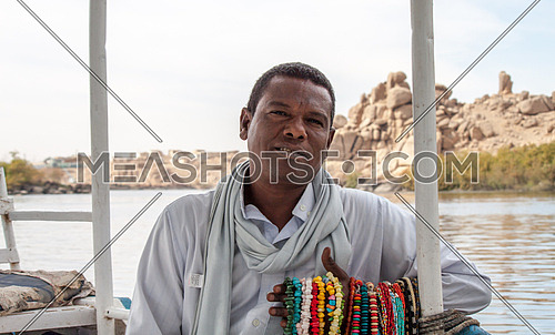 a Nubian man sitting by the nile selling accessories