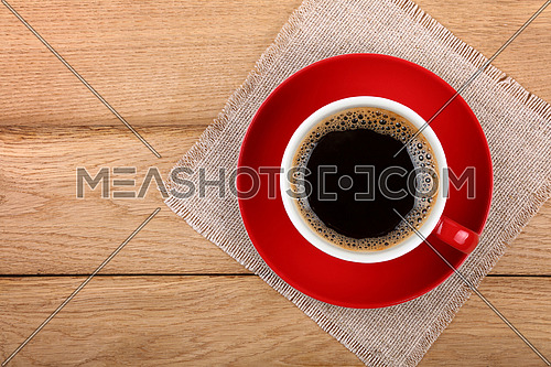 Full big cup of black instant coffee with froth on red porcelain saucer over wooden table with textile tablecloth napkin, close up, elevated top view, directly above