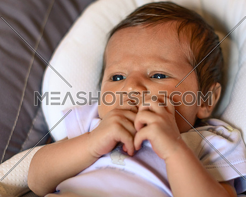 Thoughtful newborn boy looking left side with concentrated look and hand in the mouth,in his crib.