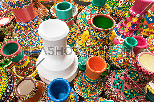Angled view showing a composition of artistic painted handcrafted colorful pottery vases with one white vase placed in the center of interest