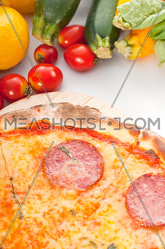 Italian original thin crust pepperoni pizza with fresh vegetables on background
