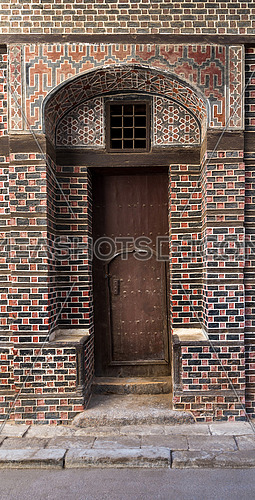 Grunge narrow wooden decorated arched entrance gate with inner small wooden door on wall with black and red bricks with white seam