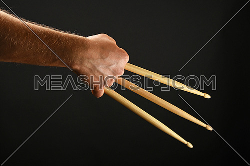Famous wolverine claws heroic gesture, man hand holding three wooden drumsticks over black background, back view, horizontal