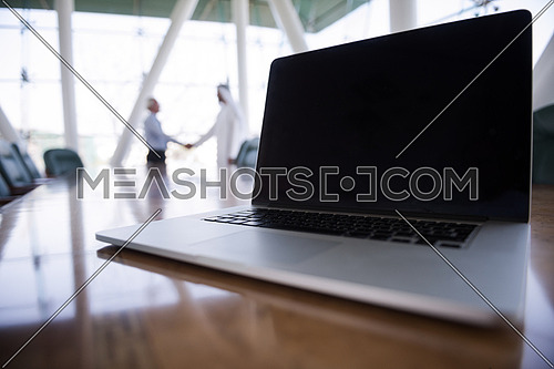 laptop computer on table while business men shake hands in background