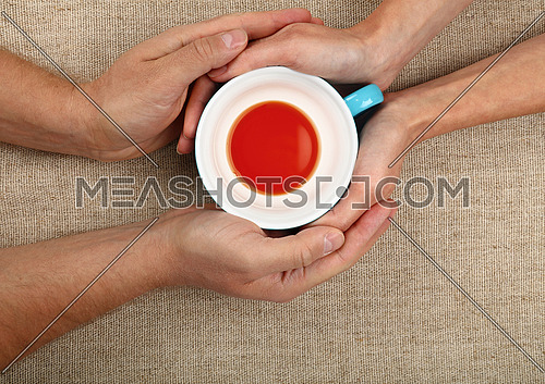 Man and woman hands holding and hugging together big empty cup of black tea over canvas tablecloth, close up, elevated top view