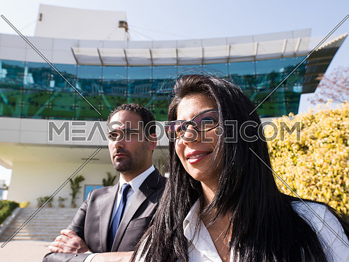 confident young business couple looking in future and standing in front of modern corporate building