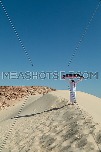 Bedouin man holding Egyptian Flag in Sinai Trail from Ain Hodouda at day.