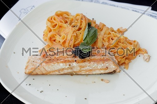 a piece of grilled salmon and some tagliatelle pasta with red sauce