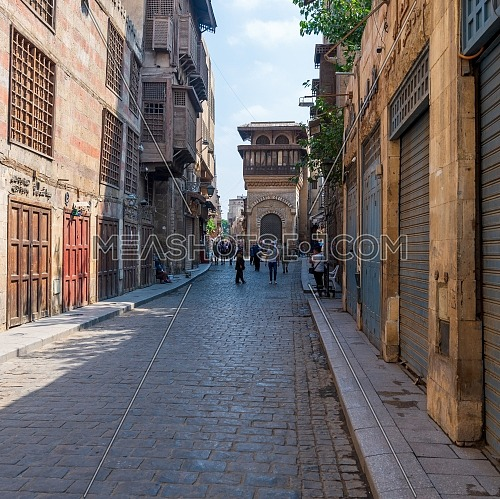 Cairo, Egypt- June 26 2020: Moez Street with few local visitors and Sabil-Kuttab of Katkhuda Mamluk era historic building at the far endduring Covid-19 lockdown period, Gamalia district, Old Cairo