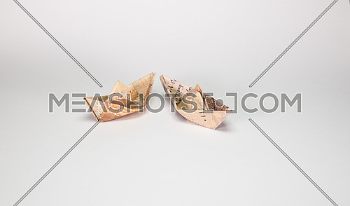 Two Egyptian Pound notes folded like paper boat floating concept