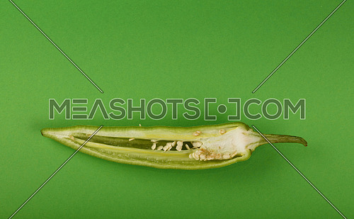 One cut half of fresh jalapeno hot chili pepper on green paper background, close up, elevated top view