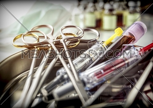 Several scissors of suture and syringes in an operating theater, conceptual image