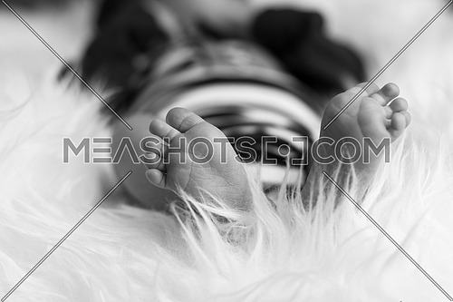 newborn bare foot surrounded by white fur