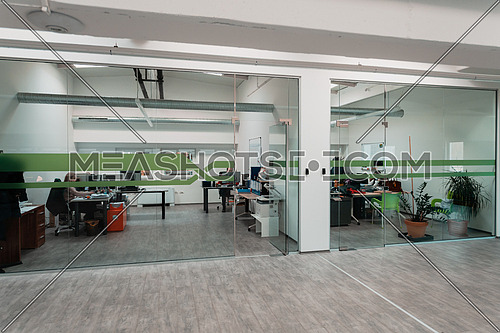 A modern glass office in the industry. Office with computers, tablets, and modern devices. High quality photo