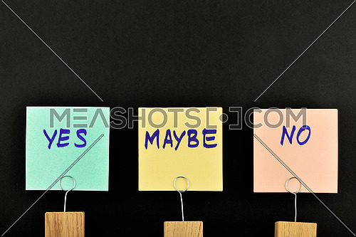 Yes, no, maybe, three paper notes, green, yellow, pink, with wooden holder isolated on black paper background for presentation