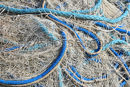 Close up background of heap coils of sea fishing net with colorful vivid floats and cable ropes at harbor