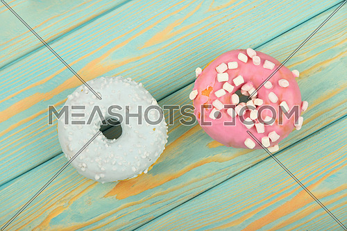 Two round ring donuts, one in blue glaze with white sprinkles topping decoration and pink with small marshmallows on painted blue vintage surface