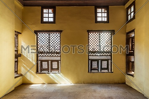 Facade of two Interleaved grunge wooden ornate windows - Mashrabiya - in stone wall in abandoned building