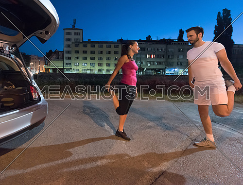 jogging couple warming up and stretching before evening running in the city