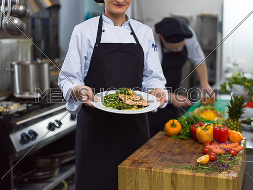Chef holding fried Salmon fish fillet with vegetables for dinner in a restaurant kitchen