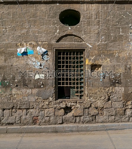 Old abandoned stone bricks wall with one closed grunge broken wooden window covered by wooden grid, Dard El Ahmar district, Cairo, Egypt