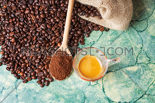 Coffee beans in coffee burlap bag on green surface,wooden spoon with ground coffee on top and coffee glass cup, view from above
