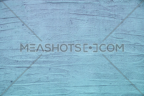 Rough uneven blue wall surface of decorative wavy embossed painted lime plaster background texture, close up