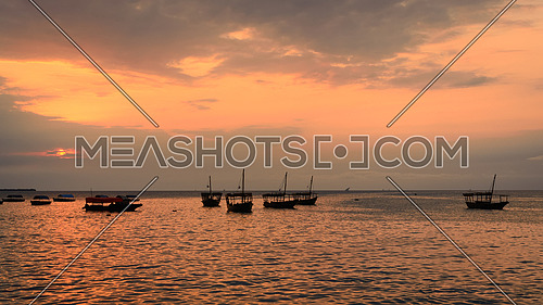Colorful horizontal photo of traditional dhow boats on open sea on Indian Ocean close to Stone Town on Zanzibar, Tanzania in East Africa, at orange sunset.