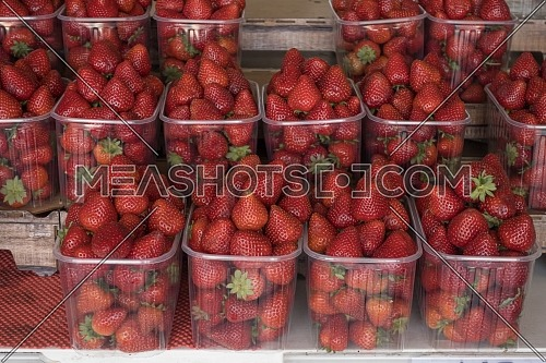 Big baskets of red ripe strawberries for sale in the street shop.