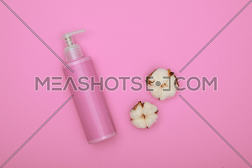 Close up one bottle of shower gel, shampoo or body care beauty product and white cotton flower over pastel pink background, elevated top view, directly above