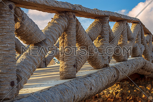 Wooden fence made of palm trunks with partly cloudy sky in sunrise time at Montaza public park in summer time, Alexandria, Egypt