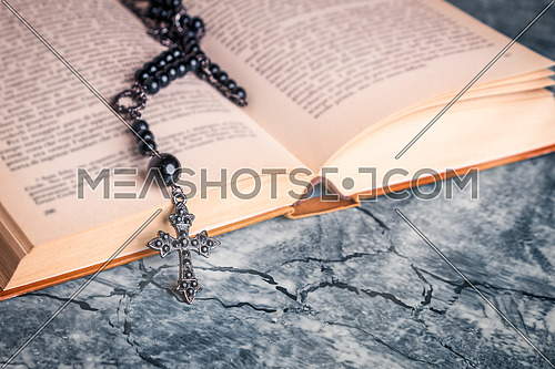 Black rosary and cross on the Bible on a gray table. Religion at school.