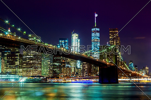 New York City's Brooklyn Bridge and Manhattan skyline illuminated at night with a full moon overhead.