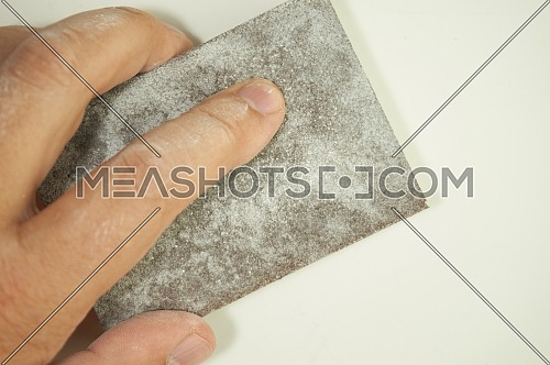 Close view of a hand sanding the wall with a sanding sponge isolated on white. Abrasive tools, DIY, copy space.