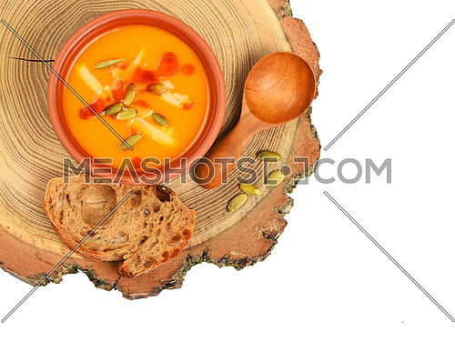 Small ceramic bowl of pumpkin cream soup, wooden spoon, slice of bread and seeds on wood cut isolated on white background, top view