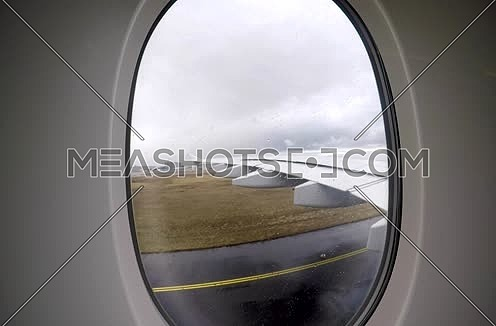 shot from plane window showing wing and runway while the plane is running