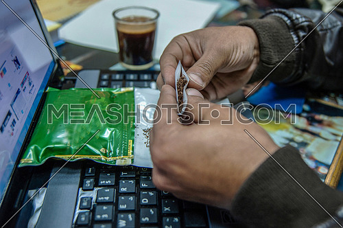A man rolling a tobacco cigaret  on desk with laptop