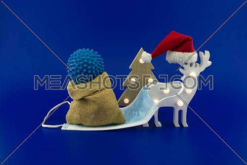 Christmas deer scene with coronavirus gift in sack bag on the sleigh made of medical face mask. Concept of holidays during covid pandemic isolated on blue background