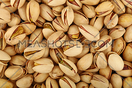Background texture of fresh roasted pistachio nuts, elevated, high angle top view, directly above