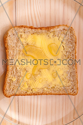 slice of whole grain bread with butter and honey