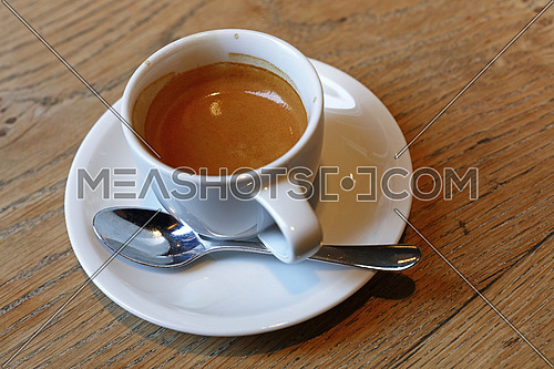 Close up one white porcelain cup of espresso coffee with saucer and spoon on wooden table, high angle view, personal perspective